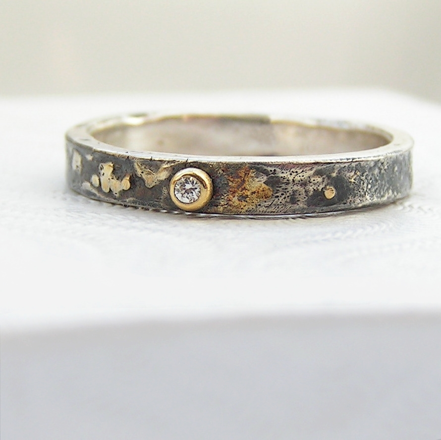 Gold Chaos Tiny Diamond: The band is made from sterling silver, textured with reticulation and oxidized. Gold accents are solid 18kt gold. It is random mix of gold dust, microgranules and solder fused to silver surface. Diamond is 1.5 mm, SI quality, near colorless (G/H) and conflict free. Set in neat gold ball.