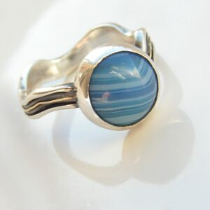 River Ring: The Band is handcrafted from silver sheet and various wires. It is embellished with thin solid yellow gold wire in center. The wavy shape of the band is unique and resembles flowing water.