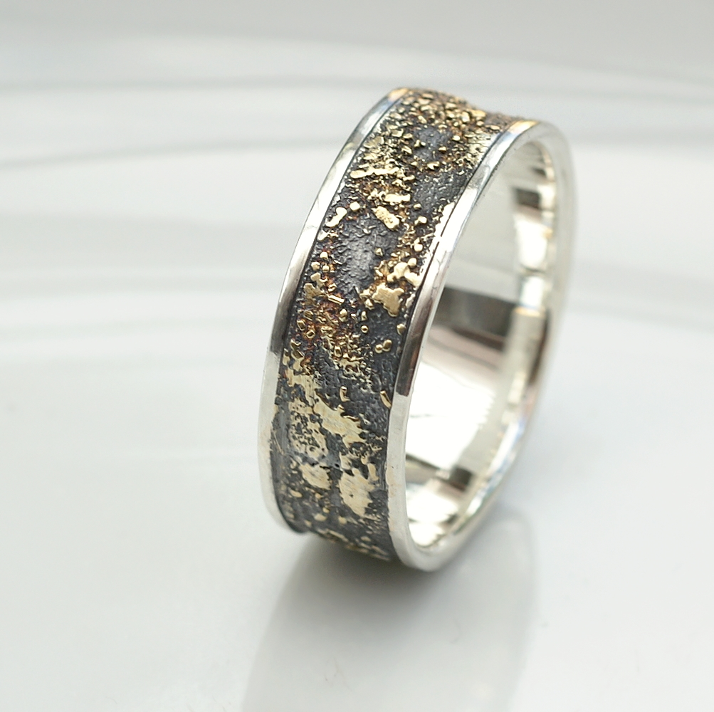 Gold Chaos with Silver Edges: The ring is made of sterling silver, slightly textured with reticulation and oxidized. Gold spots are solid 18kt gold. It is random mix of gold dust, microgranules and solder fused to silver surface. The edge is solid 18k gold.